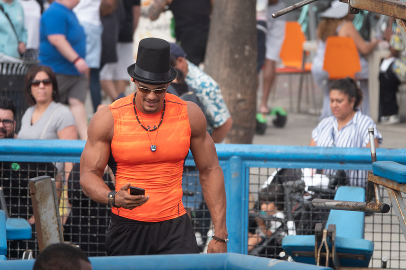 This body builder is hard to miss, in his bright orange workout shirt and top hat.