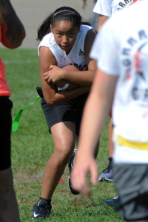 . A participant takes a handoff during Jen Welter�s Gridiron Girls Flag Football Camp on Sunday, August 12, 2018 at Mountain View High School in Loveland, Colorado. (Sean Star/Loveland Reporter-Herald)