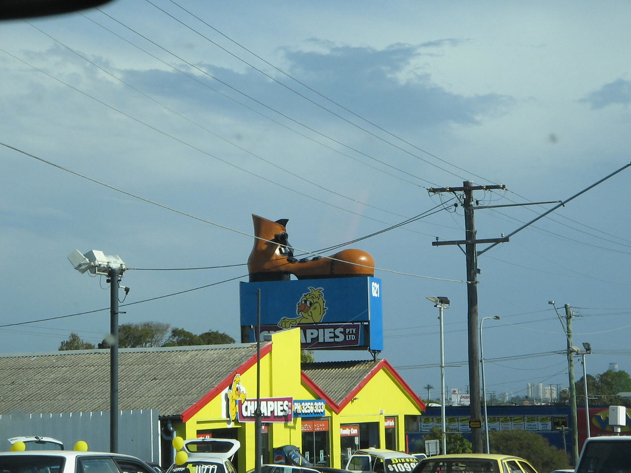 inexplicably, there is a big shoe on the top of this car lot.  ill accept any theories anyone might have?