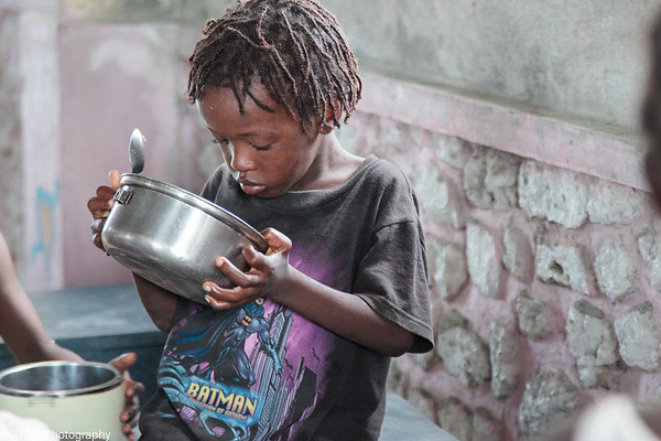 A boy looks at the bottle of his bowl, realizing he is still hungry