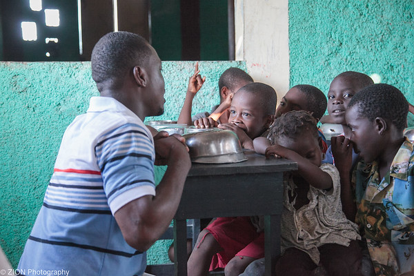 A young man named Chancely teaching children at a feeding program in Jeremie, Haiti