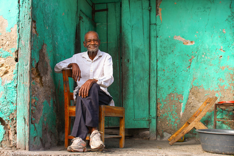 A man in Jeremie, Haiti sits on his front porch