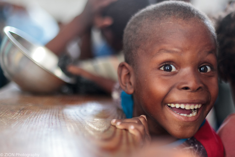A boy in Haiti becomes exited about eating at a feeding program in Jeremie