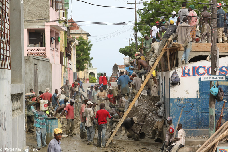 Men in Jeremie, Haiti work to pour concrete by passing buckets by hand