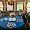 Mixed greenery and magnolia adorn the window seat of the sunny breakfast nook, as well as a fresh centerpiece arrangement of white roses, avocados and votive candles, and a royal-blue linen tablecloth, glassware and flatware color to match.