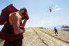 Konchog, Buddhist monk, blocks the dust as helicopter lands at Maratika, Nepal, by Mannie Garcia