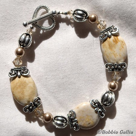 Fossil Coral Bracelet, B090100900-22  Sand colored fossil corral beads with pewter and crystal beads and toggle heart shaped clasp.