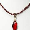 "#14620<br>Crystal drop on faceted garnet.<br>Antiqued bronze clasp and 4"" extender chain.<br>16"" to 20"" Limited Edition.<br>$99.00"