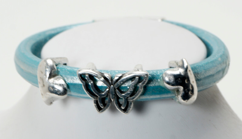 #24815B<br>Pewter butterfly and hearts<br>On metallic sky blue leather. Available in small, small/medium and medium.<br>$95.00