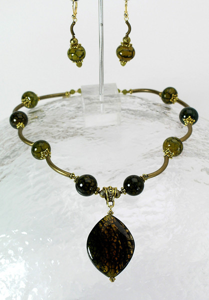 """#25912 <br>Green fire agate, Bronze, jade and antiqued brass tubes. <br>Gold plated clasp and 4"""" antiqued brass extender chain.<br>Alice Bailey Designs signature tag. Limited Edition.<br> Necklace 17""""  to 21""""  $115.00<br>Earrings with gold plated French clips $43.00"""