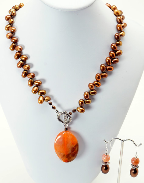 """#19519<br>Fire agate drop on<br>Leaf drilled bronze pearls.<br> Pewter toggle clasp.18""""<br>Necklace $115.00 Earrings $27.00"""