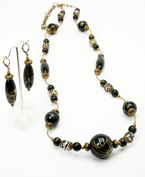 "#19418<br>Black and gold acrylic beads with<br>Antiqued bronze caps, spacers and tubes.<br>Antiqued bronze clasp and 4"" extender chain.<br>32"" to 36"" Limited Edition.<br>Necklace 79.00<br>Earrings $25.00"