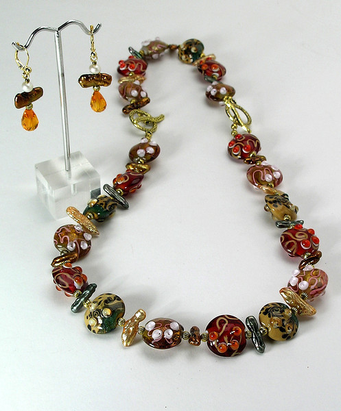 "#11814 <br>Multi colored lamp glass, biwa pearls and bronze. <br>Bronze toggle clasp. <br>Necklace 17"" Limited Edition $115.00 <br>Earrings with gold plated French clips $27.00<br>Shown using bracelet as necklace extender to 25""<br> See #11814B in ""Bracelets Gallery"""