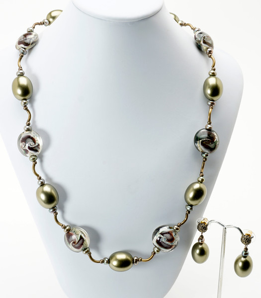 "#21919<br>Olive shell pearls, lamp glass <br>And antiqued bronze tubes.<br>Antiqued bronze clasp and 4"" extender chain.<br>32"" to 36"" Limited Edition.<br>necklace $125.00<br>Earrings $29.00"
