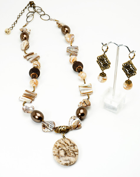 """#15018<br>Graphic feldspar drop<br>On shell, shell pearl, bronze mesh and tubes.<br>Antiqued bronze clasp and 4"""" extender chain. <br>28"""" to 32"""" Limited Edition. <br>Necklace $150.00<br>Earrings with antiqued bronze French clips $28.00"""