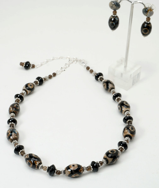 "#12417 <br>DZI agate, black onyx, smokey quartz and pewter. <br>Silver plated clasp and 4"" extender chain. <br>Necklace 16"" to 20"" Limited Edition $75.00<br>Earrings with agate and surgical steel posts $34.00"