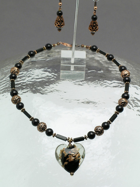 "#10309<br> Large copper &amp; black glass heart on black onyx, glass pearls and copper with copper clasp and 4"" extender chain. <br>Alice Bailey Designs signature tag.<br>Necklace 16"" to 20"" Limited Edition $75.00<br> Earrings with hypo-allergenic Niobium ear wires $35.00"