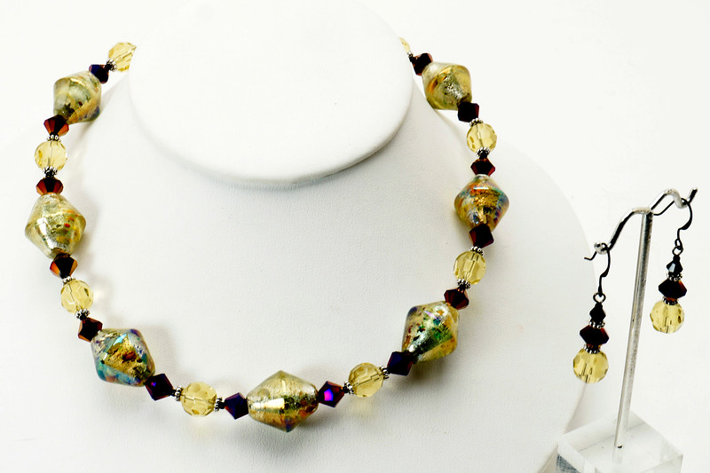 """#22119<br>Lamp glass, olivine and metallic violet crystal.<br> Nite black clasp and 4"""" extender chain.<br>16"""" to 20"""" Limited Edition.<br>Necklace $50.00<br>Earrings $24.00"""