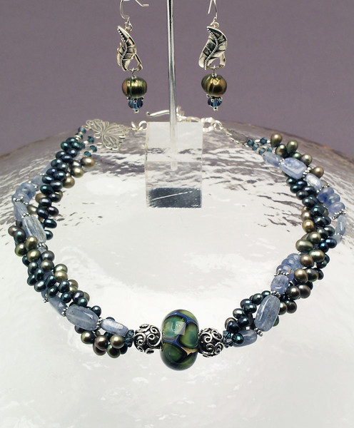 "#15610 <br>One-of-a-kind art glass bead on sterling silver, <br>kyanite, pearls and Swarovski crystal. <br>Sterling silver clasp and 4"" extender chain.<br>Alice Bailey Designs signature tag.<br>Necklace 16"" to 20"" One-of-a-kind. $350.00<br> Earrings with sterling silver leaf links and ear wires $75.00"