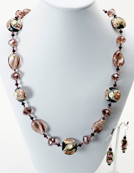 "#22019<br>Lamp glass, plum and black crystal.<br>Nite black clasp and 4.5"" extender chain.<br>23"" to 27"" Limited Edition.<br>Necklace $95.00<br>Earrings $28.00"