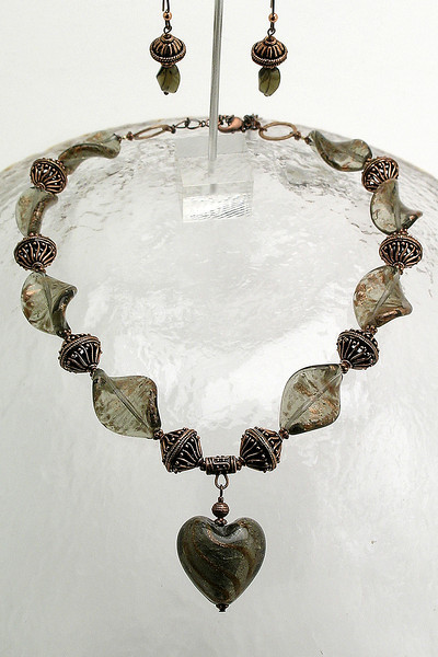 "#24412 <br>Lamp glass heart on antiqued copper and lamp glass twists. <br>Copper lobster clasp and 4"" extender chain.<br>Alice Bailey Designs signature tag.<br>Necklace 19"" to 23"" Limited Edition $125.00<br>  Earrings with hypoallergenic niobium ear wires $41.00"