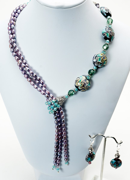 "#11218<br>Lamp glass,lilac pearls <br>and Swarovski crystal faux lariat. <br>Silver plated clasp and 4"" extender chain. <br>Alice Bailey Designs signature tag.<br>16.5"" to 20.5"" Limited Edition.<br>Necklace $195.00<br> Earrings with silver plated French clips $30.00"