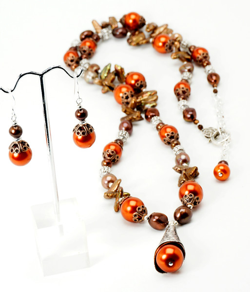 "#23618<br>Brick orange glass pearls, chocolate fresh-water pearls<br>Pewter and copper.<br>Silver plated clasp<br>And 3"" extender chain.<br>33"" to 36"" Limited Edition.<br>Necklace $150.00<br>Earrings$25.00"