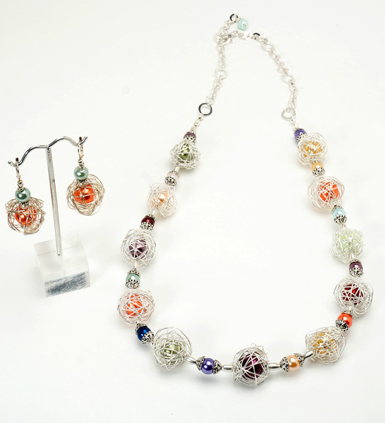 "#21217<br> Multi-colored glass pearls <br>Caged in silver wire wrapped balls. <br>Silver plated clasp and 4"" extender chain.<br>Necklace 30"" or less. Limited Edtion.<br>Necklace $155.00<br>Earrings with silver plated French clips $32.00"