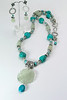 "#10914 <br>Carved jade, turquoise and pewter. <br>Extra large fancy pewter lobster claw clasp <br>and 4"" extender chain.<br>Alice Bailey Designs signature tag. <br>Necklace 30"" to 34"" Limited Edition $175.00<br>Earrings with pewter and surgical steel posts $39.00"