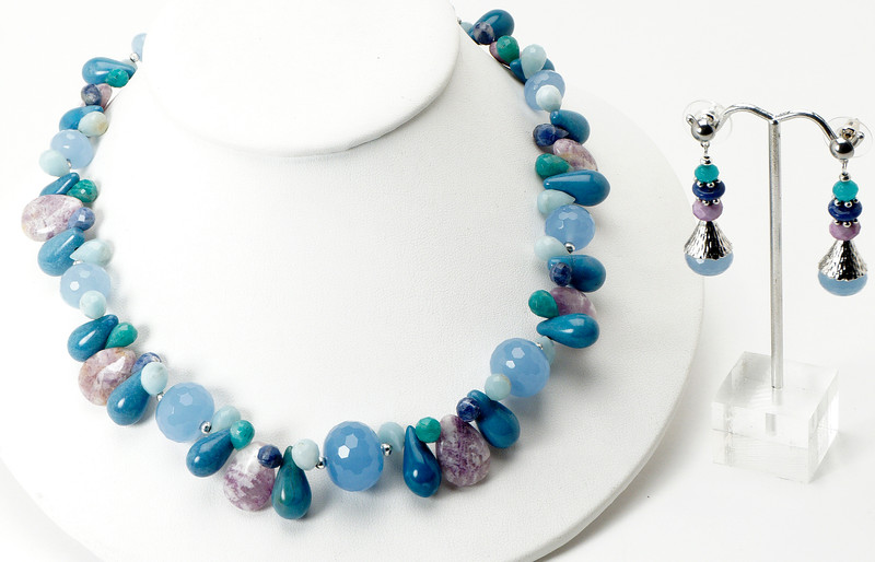 "#23718<br>Graduated, faceted periwinkle blue chalcedony,<br>Denim magnesite, sodalite,Russian amazonite,<br> Green aventurine, crazy lace agate and color-treated jade.<br>Silver plated clasp<br>And 4"" extender chain.<br>18"" to 22"" Limited Edition.<br>Necklace $135.00<br>Earrings$29.00"
