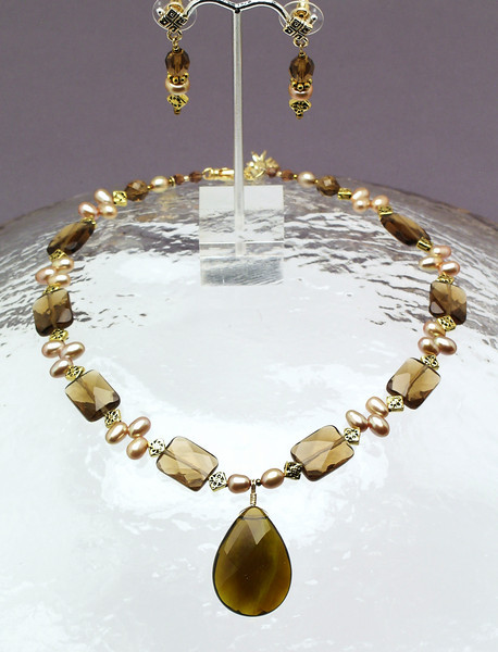 "#15810<br> Amber quartz drop on pearls, bronze and amber quartz. <br>Gold plated clasp and 4"" extender chain.<br>Alice Bailey Designs signature tag.<br>16"" to 20"" Limited Edition.<br>Necklace  $85.00<br> Earrings with bronze and surgical steel posts $32.00"