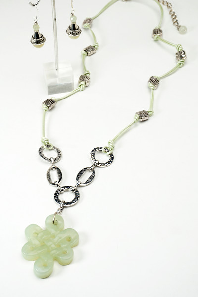 """#24016 <br>Carved new jade, silver plated chain, pewter and leather. <br>Silver plated clasp and 4"""" extender chain.<br> 29"""" to 33"""" Limited Edition $115.00<br> Earrings with silver plated French clips $27.00<br>Note: natural stones will vary."""
