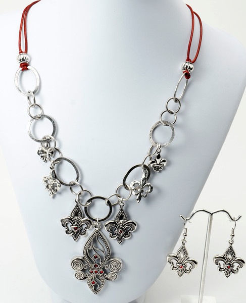 "#12017C <br>Pewter Fleur de Lis and ruby Swarovski crystal drops <br>on silver plated chain and distressed red leather. <br>Silver plated clasp and 4"" extender chain. <br>Necklace 19"" to 23"" Limited Edition $49.00<br>Earrings with surgical steel ear wires $17.00"