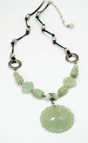 "#11718<br>Carved jade pewter and metallic silver leather.<br>Silver plated clasp and 4"" extender chain.<br>28"" to 32"" Limited Edition.<br> Necklace $125.00"