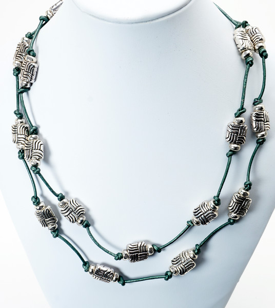 "#10418<br> Pewter on jade green leather.<br> Silver plated clasp and 4"" extender chain.<br> 37"" to 41"" or doubled at 18"" <br> Shown doubled.<br> Limited Edition $85.00"