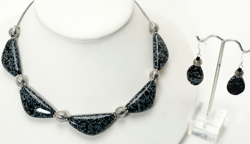 "#11620<br>Snowflake obsidian<br>And pewter. <br>On metallic silver leather.<br>Silver plated clasp <br>And 4"" extender chain. <br>16.5"" to 20.5"" Limited Edition.<br>Necklace $59.00<br>Earrings $26.00"