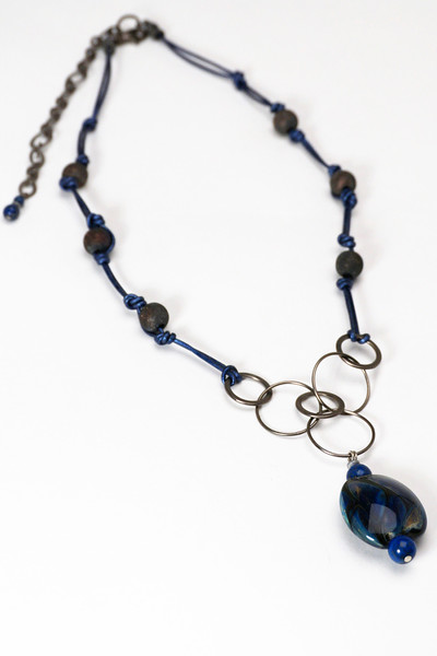 "#17116 <br>One-of-a-kind art glass and lapis drop<br> on gunmetal chain, stardust beads and metallic blue leather. <br>Gunmetal clasp and 4"" extender chain.<br>One-of-a-kind. 21"" to 25""  $125.00"