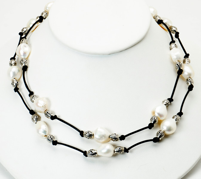 "#10118<br> Natural white pearls, pewter and black leather.<br>Silver plated clasp and 4"" extender chain.<br>36"" to 40"" or doubled at 18+"" Limited Edition.<br> Shown doubled.<br>Necklace $85.00"
