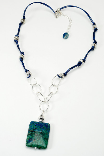 "#25516 <br>Crysocolla drop on silver plated chain,<br>pewter and blue metallic leather. <br>Silver plated clasp and 4"" extender chain.<br> Necklace 24"" to 28"" Limited Edition. $95.00<br> Note: color of these natural stones will vary slightly."