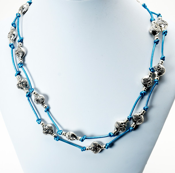 "#10318<br> Pewter on turquoise leather.<br> Silver plated clasp and 4"" extender chain.<br> 37"" to 41"" or doubled at 18"" <br> Shown doubled.<br> Limited Edition $85.00"