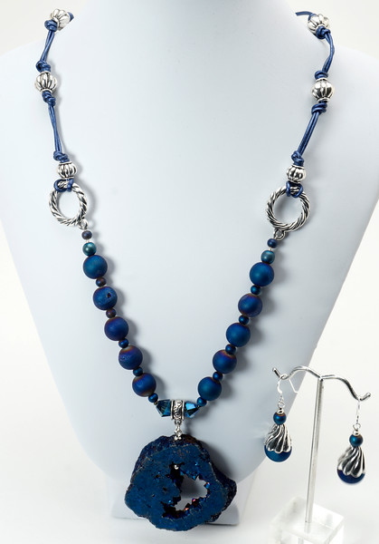 "#11418<br> Cobalt quartz geode slice <br>On quartz, pewter, crystal and metallic cobalt leather.<br>Silver plated clasp and 4"" extender chain.<br>22"" to 26"" Limited Edition..<br>Necklace $125.00 <br>Earrings wtih silver ear wires $28.00<br>Size and shape of geode slices will vary."