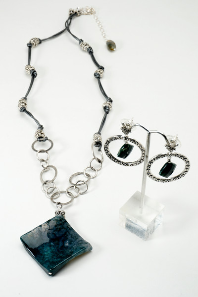 "#24516 <br>Moss agate on silver plated chain, <br>pewter and silver metallic leather.<br> Silver plated clasp and 4"" extender chain. <br>Necklace 27"" to 32"" Limited Edition $95.00<br>Earrings with pewter and surgical steel posts $34.00"