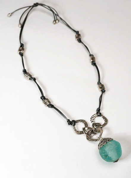 #16016 <br>Sea glass and pewter filigree drop <br>on antiqued silver plated chain, pewter and metallic silver leather.<br> Necklace Adjustable. Limited Edition $95.00