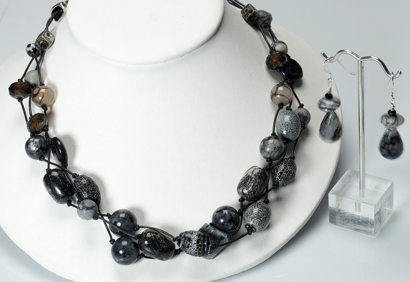 "#22819<br>Three braided strands of porcelain, obsidian, <br>crackle agate, fire agate and glass. <br>On black leather, silver plated cones,<br> clasp and 4"" extender chain.<br>18"" to 22"" Limited Edition.<br>Necklace $135.00<br>Earrings $35.00"
