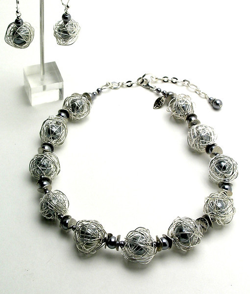 "#19114 Silver glass pearls cages in silver plated wire with steel wavy spacers. Silver plated clasp and 4"" extender chain.Alice Bailey Designs signature tag.17"" to 20"" Limited Edition. <br><br><a href=""https://www.paypal.com/cgi-bin/webscr?cmd=_cart&amp;add=1&amp;business=alice@AliceBaileyDesigns.com&amp;item_name=Alice%20Bailey%20Designs%20Item%20Number%19114%20Necklace&amp;item_number=19114&amp;amount=%24125.00&amp;return=http://www.paypal.com&amp;cancel_return=http://www.paypal.com"" target=""_click"" class=""paypalbutton"">Purchase Necklace $125.00</a><br><br> <br><br><a href=""https://www.paypal.com/cgi-bin/webscr?cmd=_cart&amp;add=1&amp;business=alice@AliceBaileyDesigns.com&amp;item_name=Alice%20Bailey%20Designs%20Item%20Number%2019114%20Earrings&amp;item_number=19114&amp;amount=%2430.00&amp;return=http://www.paypal.com&amp;cancel_return=http://www.paypal.com"" target=""_click"" class=""paypalbutton"">Purchase Earrings $30.00</a><br><br> <br><br><a href=""https://www.paypal.com/cgi-bin/webscr?cmd=_cart&amp;add=1&amp;business=alice@AliceBaileyDesigns.com&amp;item_name=Alice%20Bailey%20Designs%20Item%20Number%2019114%20Earrings%20and%20Necklace&amp;item_number=19114&amp;amount=%24155.00&amp;return=http://www.paypal.com&amp;cancel_return=http://www.paypal.com"" target=""_click"" class=""paypalbutton"">Purchase Necklace and  Earrings $155.00</a><br><br> <br><br><br><br><img src=""http://ali.smugmug.com/Other/WebSiteImages/i-BftLFq2/0/O/paypal-175-50-O.jpg""><br><font class=""captionfooter"">Free Shipment on all Orders</font>"