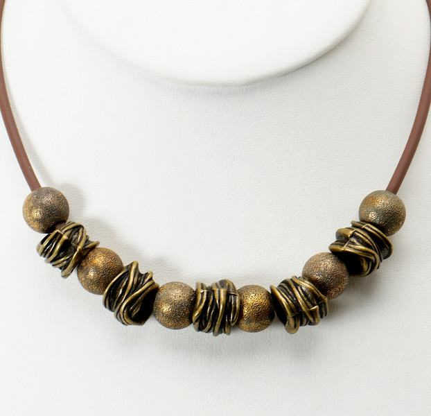 "#20219<br> Bronze brambles and stardust<br>On brown rubber cord,<br>Antiqued bronze clasp and 4"" extender chain.<br>16"" to 20"" Limited Edition.<br>$55.00"