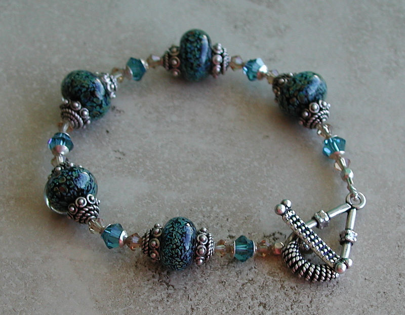 "Handcrafted ""boro"" lampwork glass beads, Swarovski crystals, imported handcrafted sterling silver beads and toggle clasp. Fits a 6-3/4"" wrist. $75.<br /> (ob2263)"