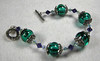 "Handcrafted lampork glass beads, these are hollow. Swarovski crystals, handcrafted sterling silver bead caps and clasp, teensy tiny French cut steel beads, circa 1900. Beautiful emerald with complimentary purple. Fits a 6-1/2"" wrist. (ob3896)"
