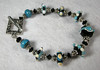 "Handcrafted lampwork glass beads, handcrafted sterling silver beads and clasp, genuine Swarovski crytals. Turquoise blue, black and ivory. This bracelet will fit a 7-1/4"" wrist. <br /> (ob3925)"