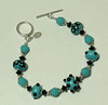"Handcrafted lampork glass beads, Swarovski crystals (the faceted turquoise blue beads), handcrafted sterling silver bead caps and clasp, sterling silverfindings. Turquoise blue and black. Fits a 7"" wrist. <br /> (ob3911)"